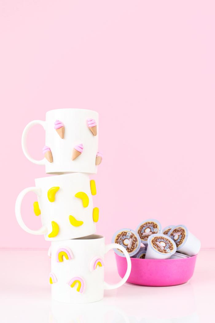 comment décorer tasses blanches avec motifs en pâte polymère, idée cadeau meilleure amie, figurine banane crème glacée et arc-en-ciel sur tasse blanche