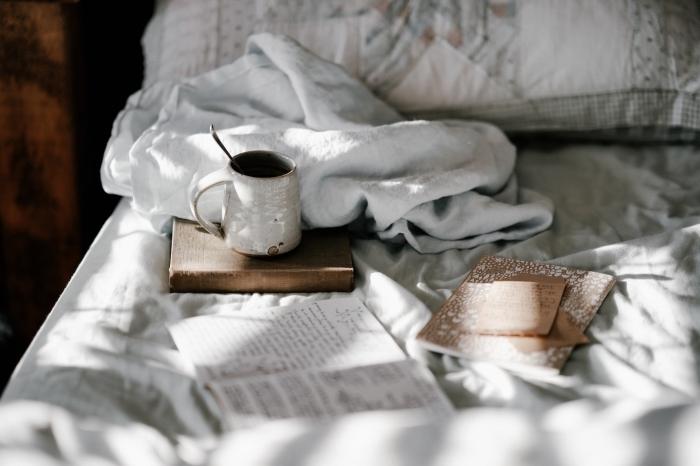 wallpaper pc avec cadre cozy d'un lit cocooning avec tasse de café et livres, exemple de fond d écran gratuit