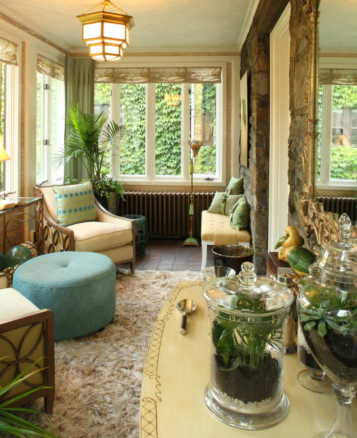 joli amenagement de veranda, tabouret turquoise, tapis oriental, fauteuil beige, grande bonbonnière