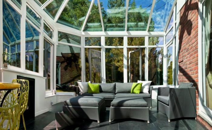 fauteuils gris, coussins verts, sol en grandes dalles grises, toiture et murs vitrés, veranda photo