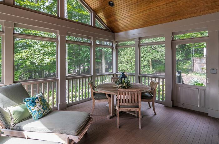 veranda moderne fermée, table ronde en bois, chaise longue, toiture en bois, fenêtres de véranda blanches