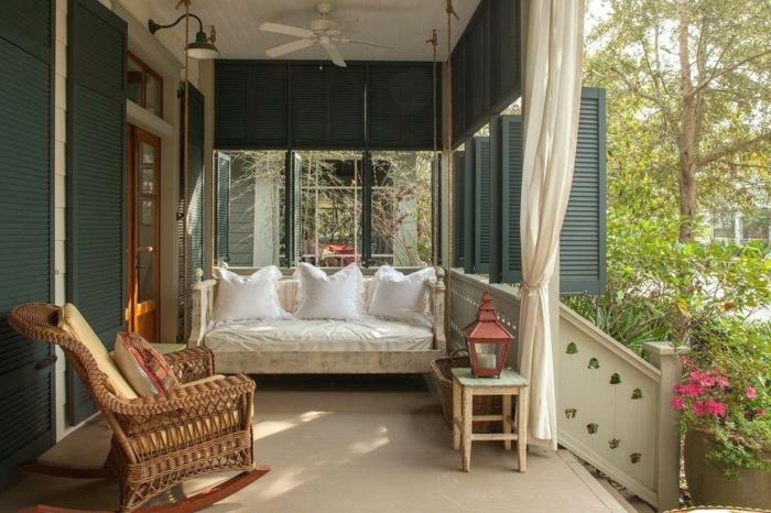 petite veranda, banquette suspendue, chaise berçante en rotin, tabouret, lanterne rouge, petit escalier