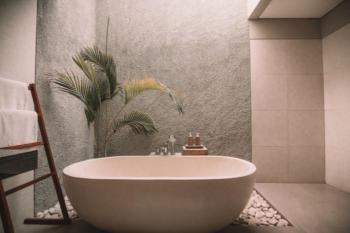 Palmier dans pot sur sol pierres zen, échelle rangement basse, salle de bain en bois et blanc, belle salle de bain moderne