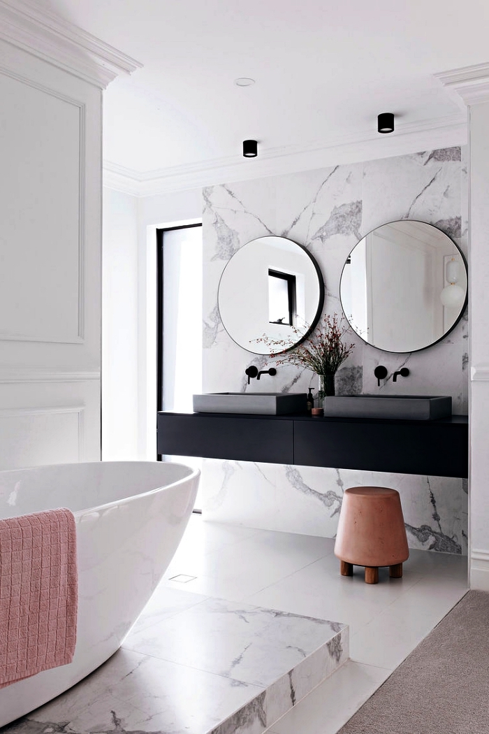 salle de bain de luxe avec crédence en marbre qui s'accorde avec le podium de la baignoire îlot, salle de bain au design épuré avec meuble sous vasque flottant en noir mat