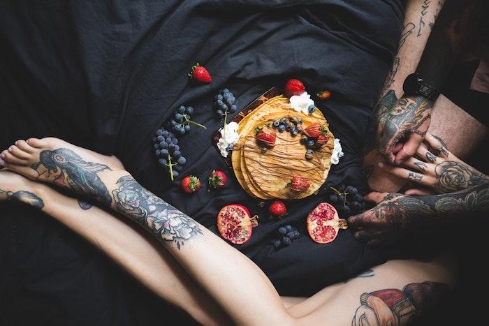 Couple tatoué, crêpes et fruits, petit déjeuner au lit, motif tatouage, dessin tatouage original, encre dessin sur la peau