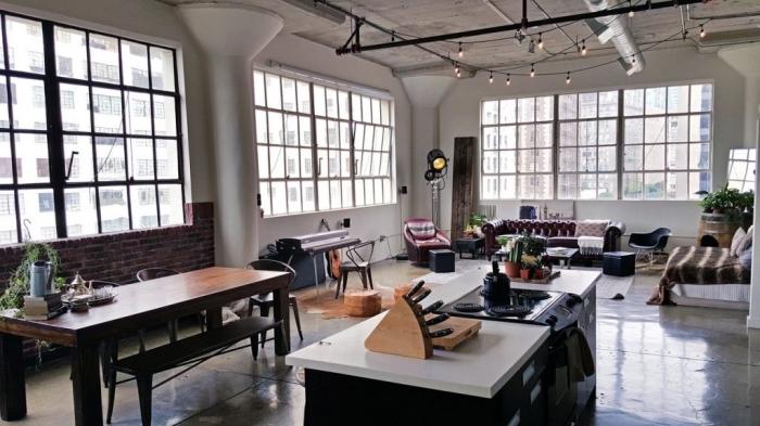 salon aux murs blancs avec deco murale industrielle en briques rouges, modèle de table à manger en bois brut
