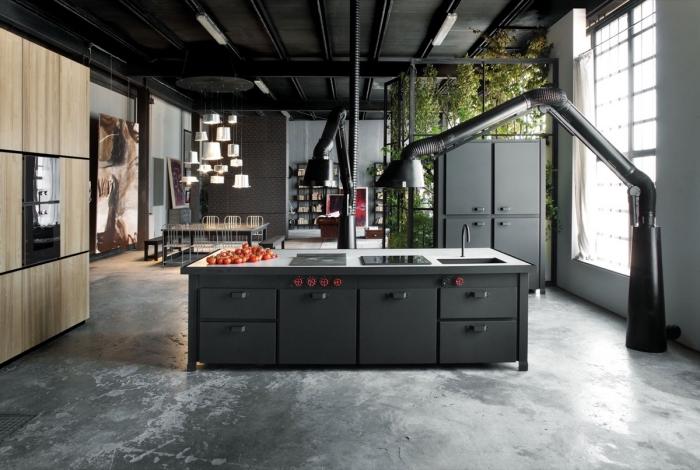 modèle de salle a manger industrielle ouverte vers la cuisine, pièce aux murs blancs avec plafond noir et plancher béton