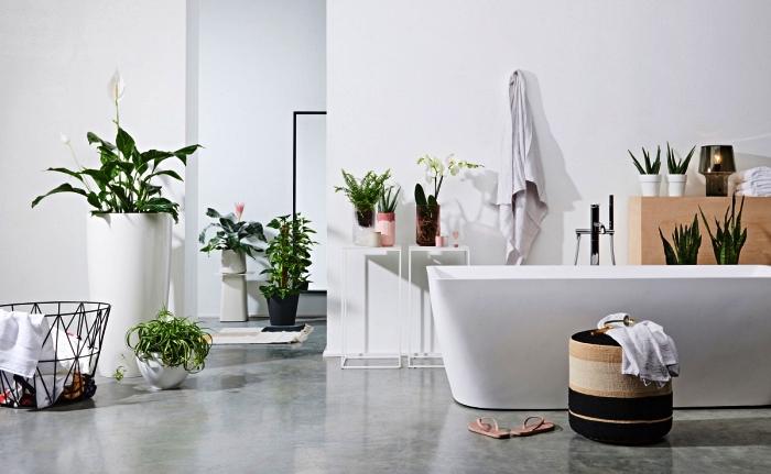 salle de bain blanche aux accents végétaux avec baignoire îlot au design moderne, des accessoires de salle de bain de style scandinave et ethnique chic