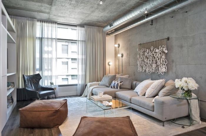 déco de salon industriel au plafond et murs béton avec parquet bois foncé, modèle de canapé en gris clair avec coussins blancs et gris