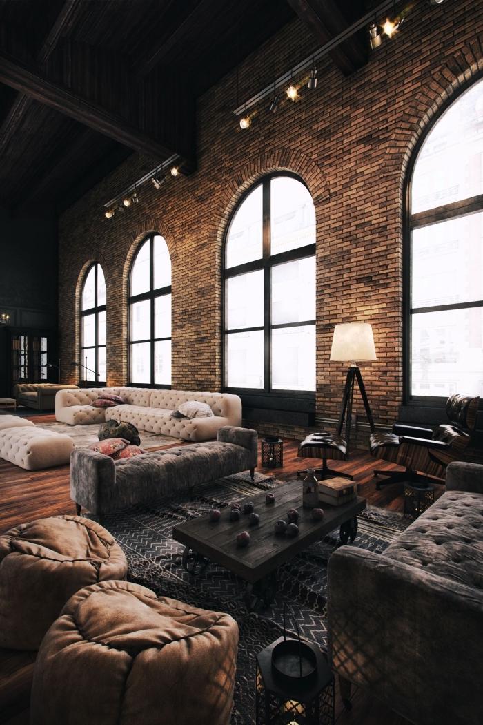 exemple de salon style industriel au plafond haut avec murs briques, meubles de salon en bois brut foncé, modèle lampe sur pied en fer