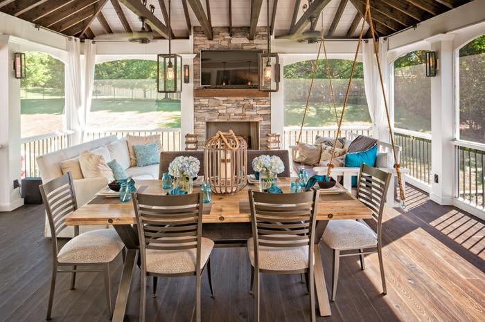 grande table en bois, chaises, poutres en bois au plafond, murs vitrés, exemple d'amenagement de veranda