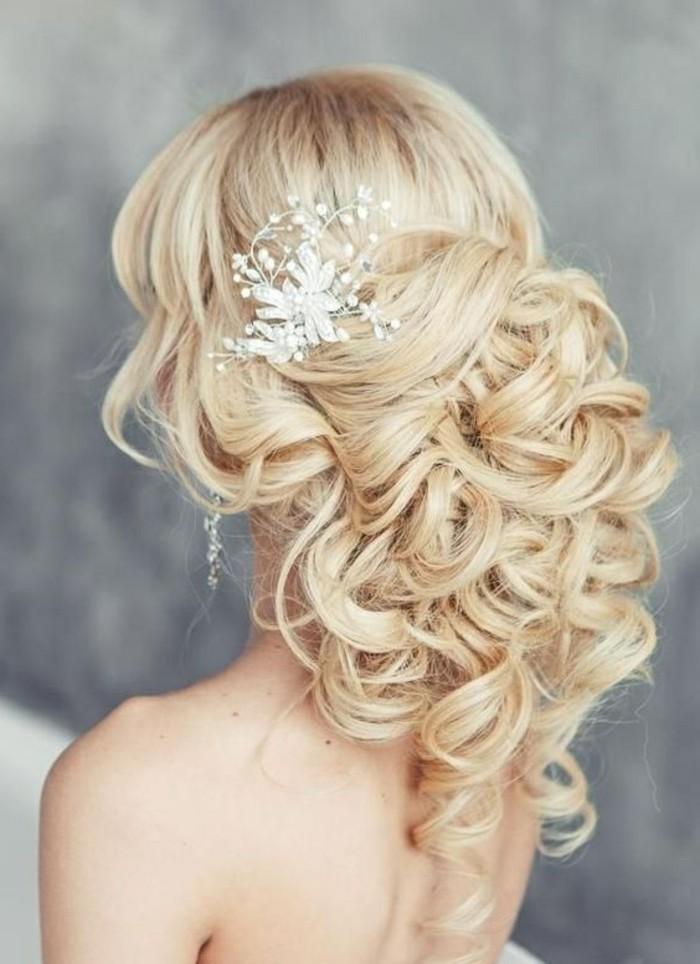 exemple coiffure mariage avec volume en arrière et boucles attachées et accessoirisées d une fleur blanche