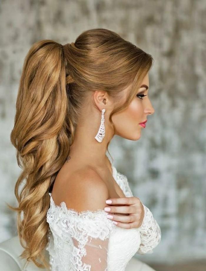 coiffure mariage avec queue de cheval haute et volume sur le dessus, couleur de cheveux blond, robe de mariée blanche en dentelle
