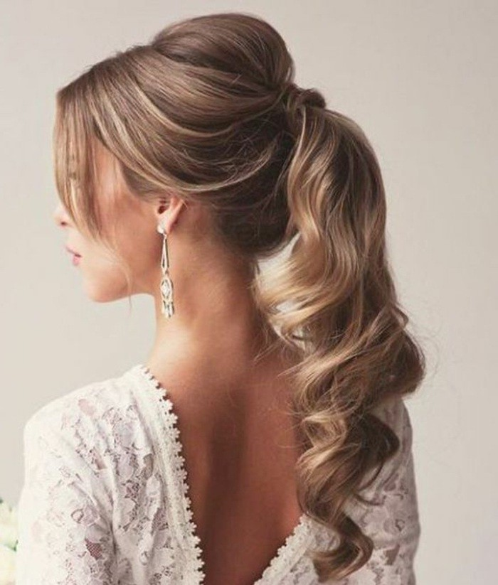 queue de cheval haute avec volume sur le dessus et boucles, mèches encadrant le visage, robe de mariée dentelle