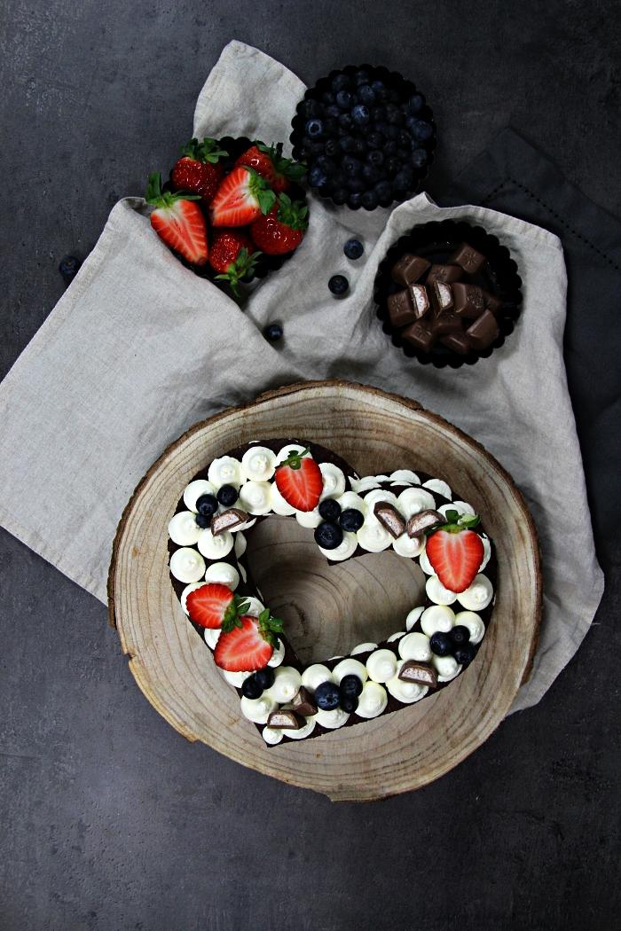 gateau coeur au chocolat en pâte sablée, gâteau en forme de coeur garni de meringues en buttercream déposé sur un rondin de bois