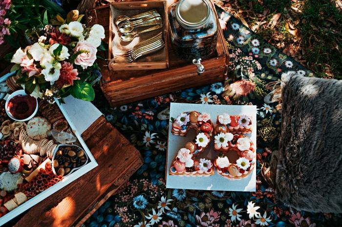 repas pour un anniversaire pique-nique, gâteau chiffre 25 ans et plateau de fromages posés au sol