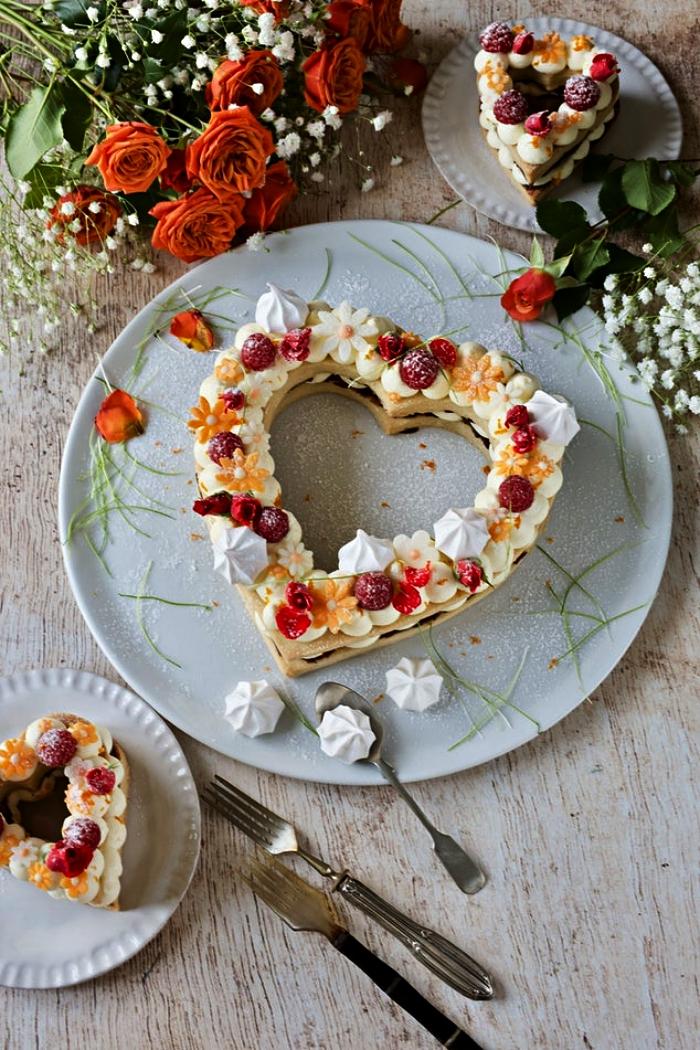 gateau coeur sur une base biscuit au décor de meringues, fruits rouges et fleurs comestibles