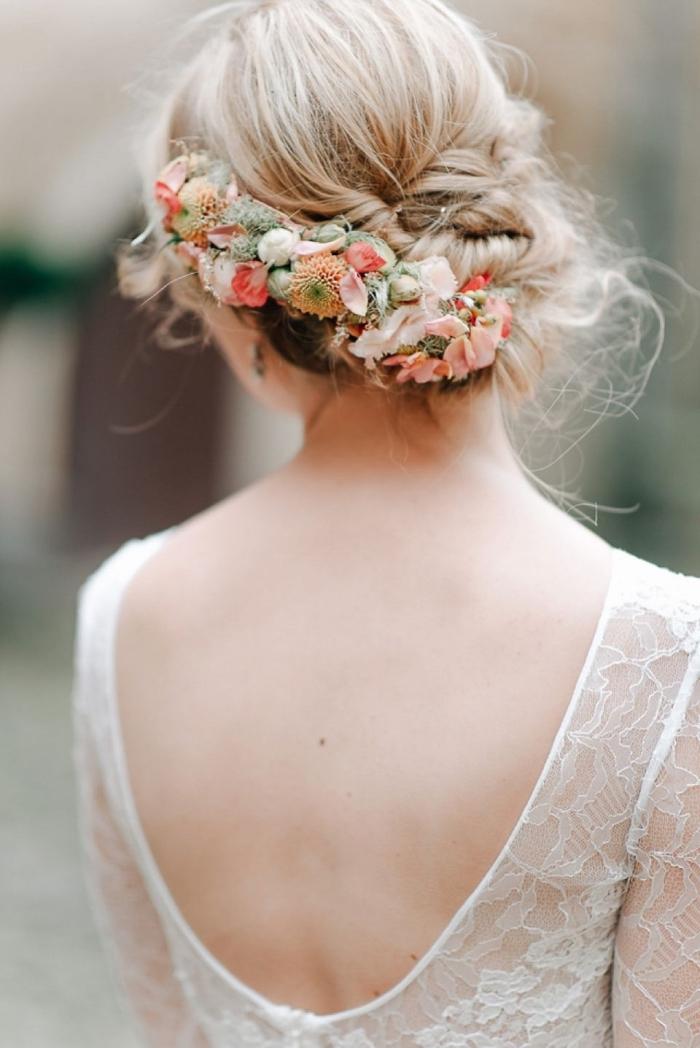 look de mariée avec coiffure mariage chignon torsadé bas accessoirisé de fleurs, coiffure avec chignon bohème