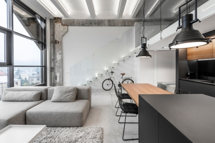 design contemporain dans un salon style industriel aux murs blancs avec plancher effet béton, modèle cuisine bois et gris anthracite