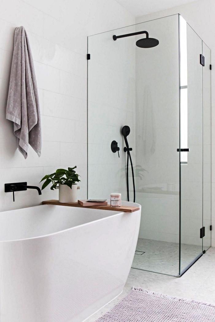 salle de bain blanche moderne avec baignoire îlot et douche italienne derrière paroi vitrée qui semble se fondre dans le décor