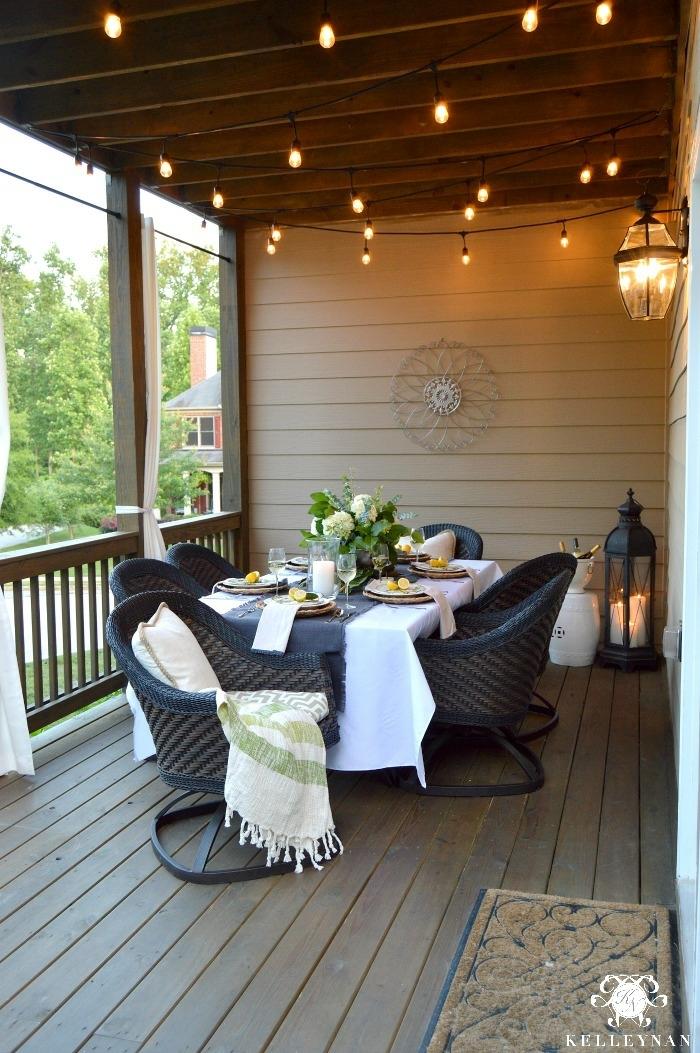 terrasse en bois, guirlande d'ampoules électriques, lanterne suspendue, veranda ouverte avec table de repas