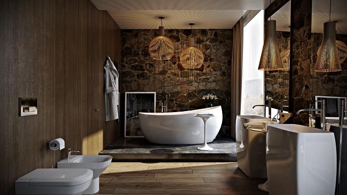 salle de bain de luxe où dominent les matériaux naturels avec baignoire zen sur podium en béton mis en valeur par un mur en pierre naturelle