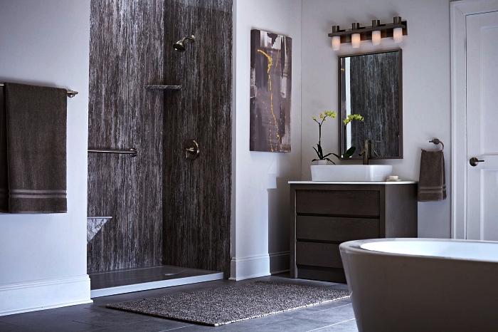 modèle de salle de bain zen et nature en blanc et gris avec douche qui s'ouvre à l'espace aux parois effet pierre naturelle et une baignoire gris taupe