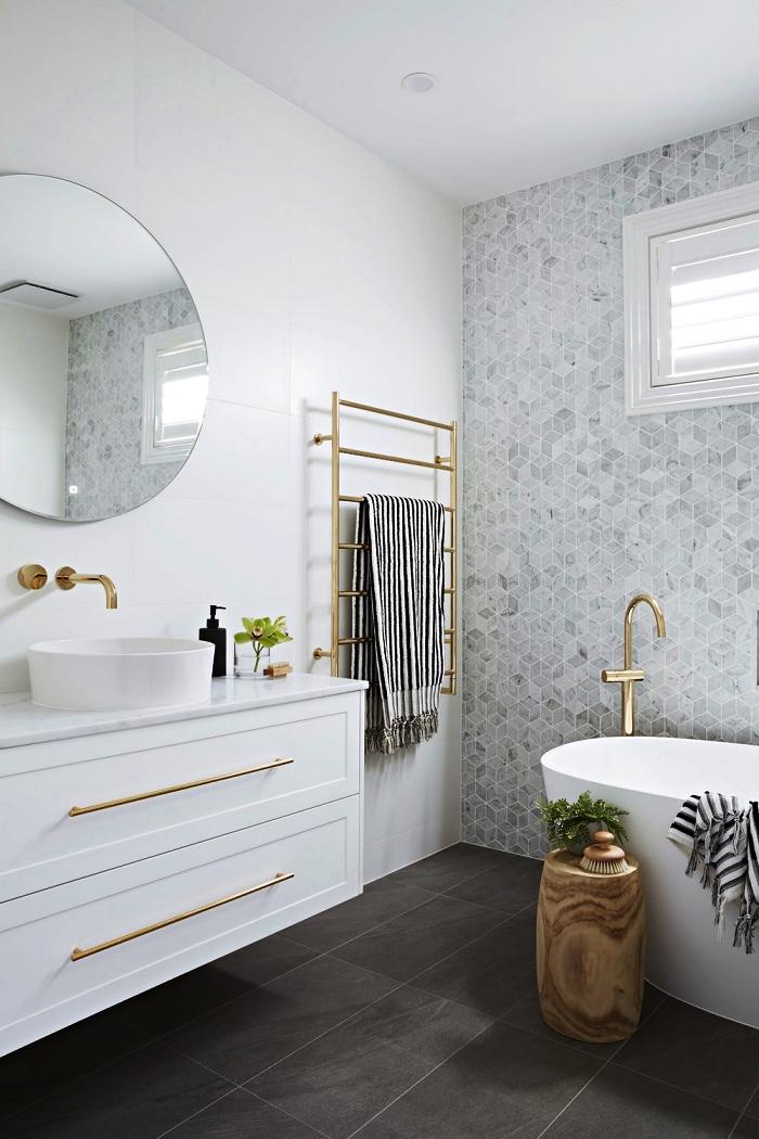 une salle de bain gris et blanc aux lignes épurées avec baignoire îlot moderne et un mur d'accent en carreaux hexagonaux en nuances du gris, robinetterie et sèche-serviettes en laiton