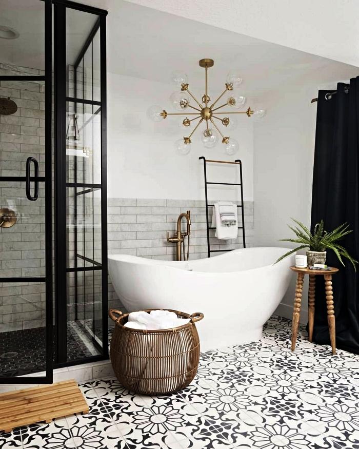 salle de bain gris et blanc au sol de carreaux de ciment, espace douche sur un plancher surélevé délimité par une verrière