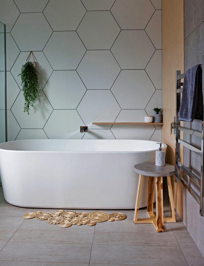 une salle de bain blanche avec baignoire ovale moderne contre un mur en panneau mural à motifs hexagonaux, déco naturelle avec tapis bohème en fibres végétales et table d'appointe en bois et béton