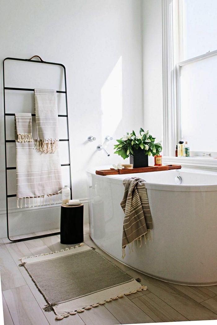 décoration de salle de bain nature avec baignoire îlot ovale et porte-serviette minimaliste en métal, revêtement de sol en parquet clair pour salle de bains