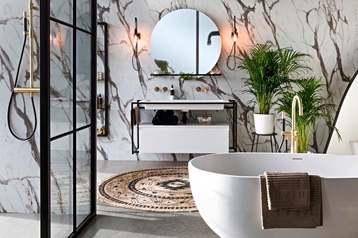 salle de bain contemporaine en marbre avec baignoire îlot aux lignes modernes et douche italienne délimitée par une verrière industrielle, salle de bains moderne esprit minimaliste et nature décorée de plantes vertes et d'un tapis rond en fibres naturelles