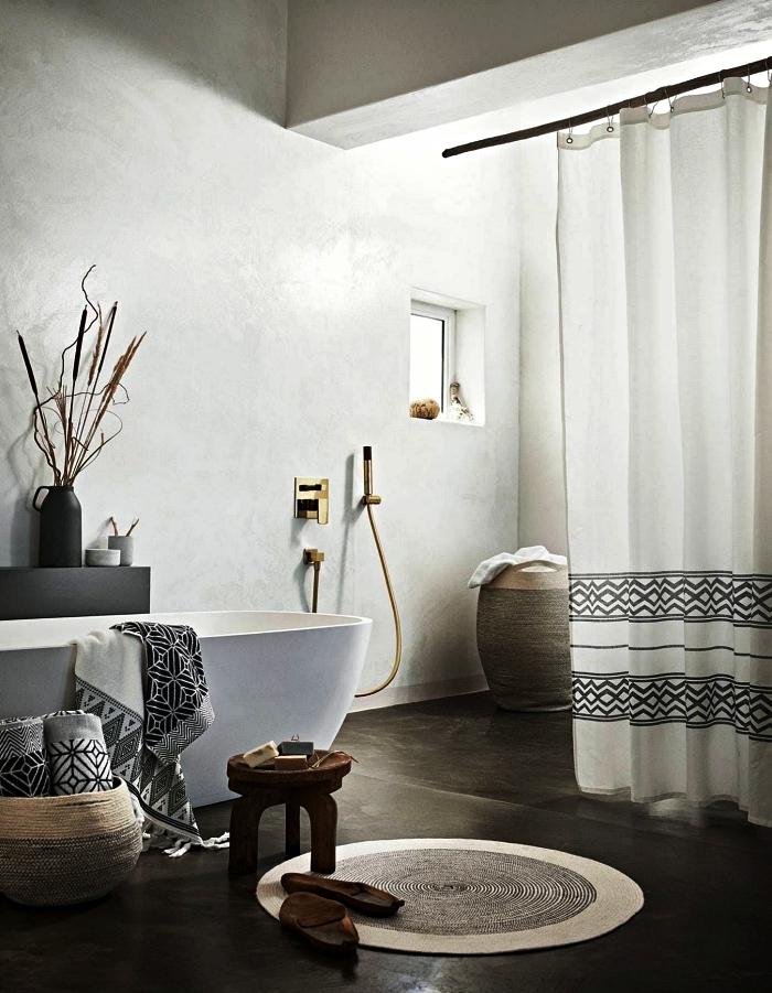 salle de bain zen en béton ciré aux accents ethniques chic, espace zen autour d'une baignoire îlot avec des paniers en fibres naturelles et des accessoires en béton