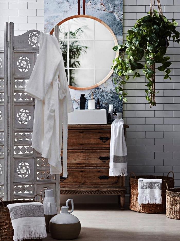 des accessoires de salle de bain nature et zen en bois d'aspect authentique et en fibres naturelles, une salle de bains au carrelage métro blanc avec meuble sous vasque chiné en bois et une jolie crédence d'aspect marbre