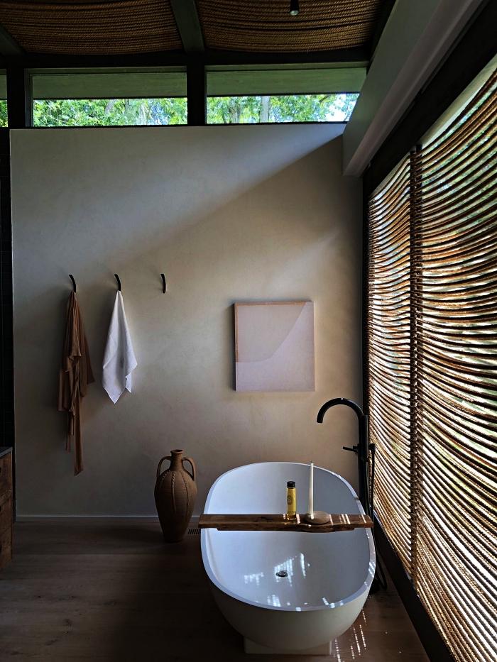 salle de bain nature et zen au design minimaliste avec baignoire îlot et une large baie vitrée qui laisse filtrer la lumière naturelle