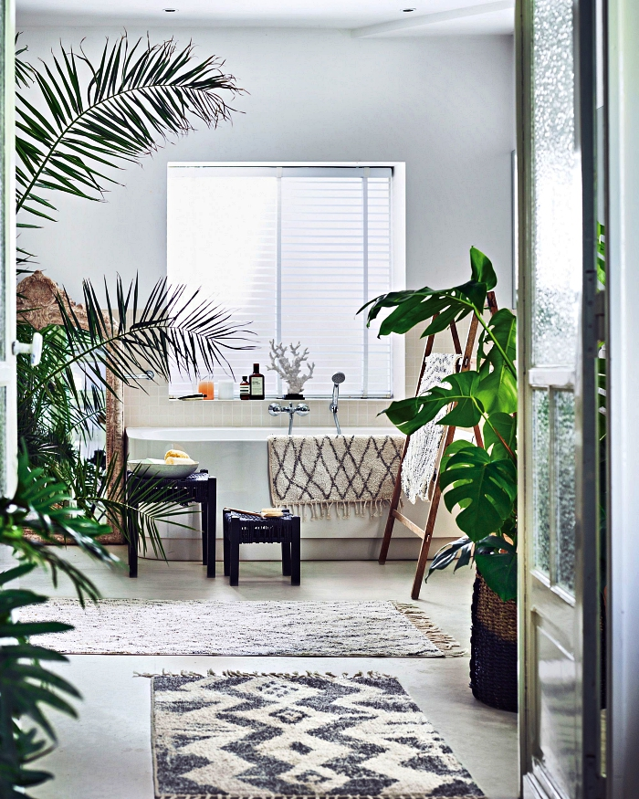 inspiration pour une salle de bain pinterest aux accents bohème et nature avec baignoire délimitée par une crédence en carrelage beige qui s'harmonise avec les tapis authentiques