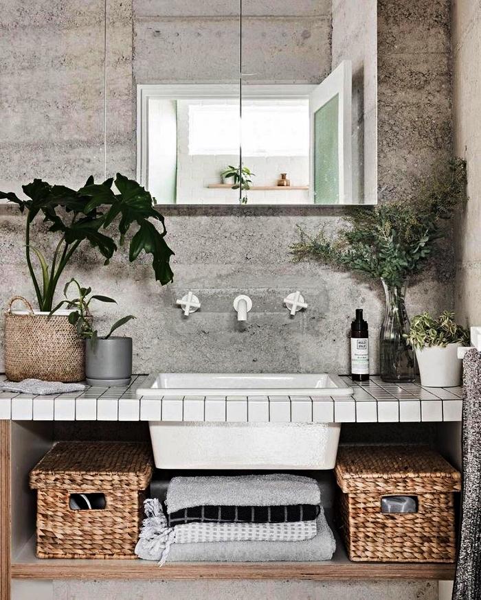 modele salle de bain d'ambiance zen et authentique d'aspect béton, meuble salle de bain avec plan vasque en carreaux blancs décoré de paniers en fibres naturelles
