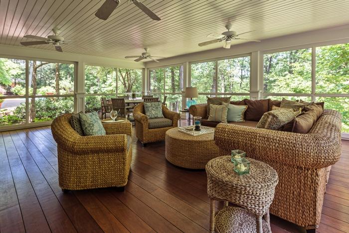 salon de jardin en rotin dans une véranda spacieuse, grandes fenêtres du plafond au sol, plafond en lattes blanches