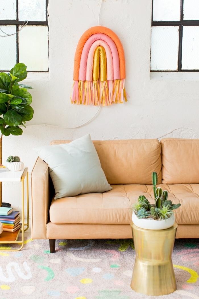 deco mural arc-en-ciel aux couleurs pastels, sofa orange pâle, grand pot de fleurs, coussin gris, table d'appoint