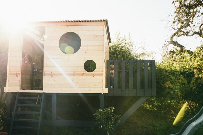 idée comment construire une cabane avec terrasse peinte en noir mate, modèle de maison bois avec fenêtre ronde