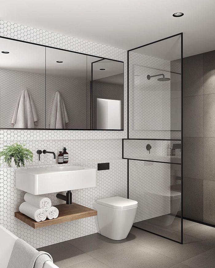 Noir métal détails dans une salle de bain grise avec carrelage blanche, salle de bain blanche et bois décoré bien