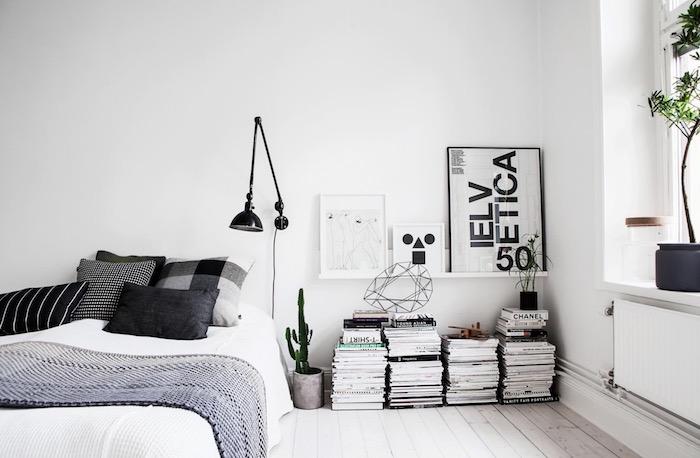 Chambre style scandinave a noir et blanc, livres rangement sur le sol en bois, lit avec rangement, astuce rangement chambre, belle chambre à coucher
