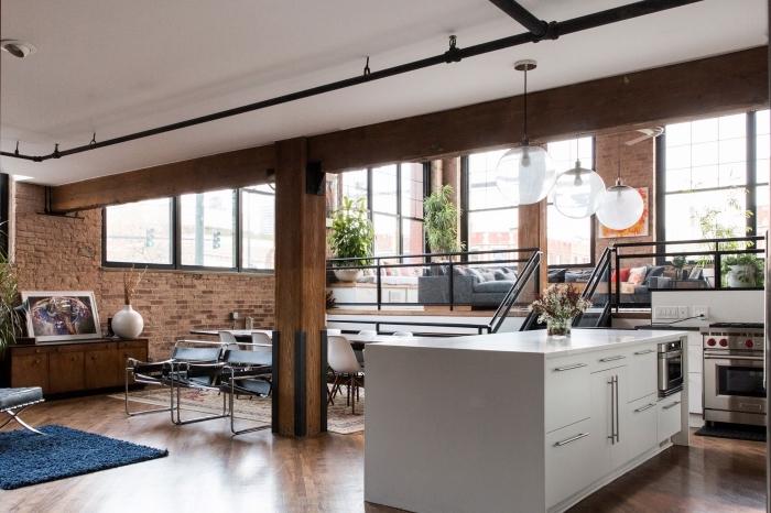 aménagement studio loft aux murs briques avec plafond blanc et parquet bois, agencement cuisine avec îlot