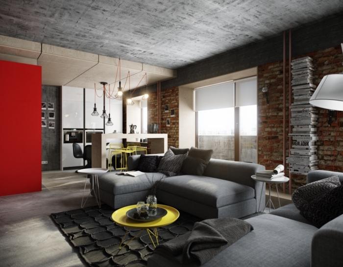 aménagement studio aux murs briques et plafond béton avec pan de mur rouge, modèle de petit canapé d'angle gris