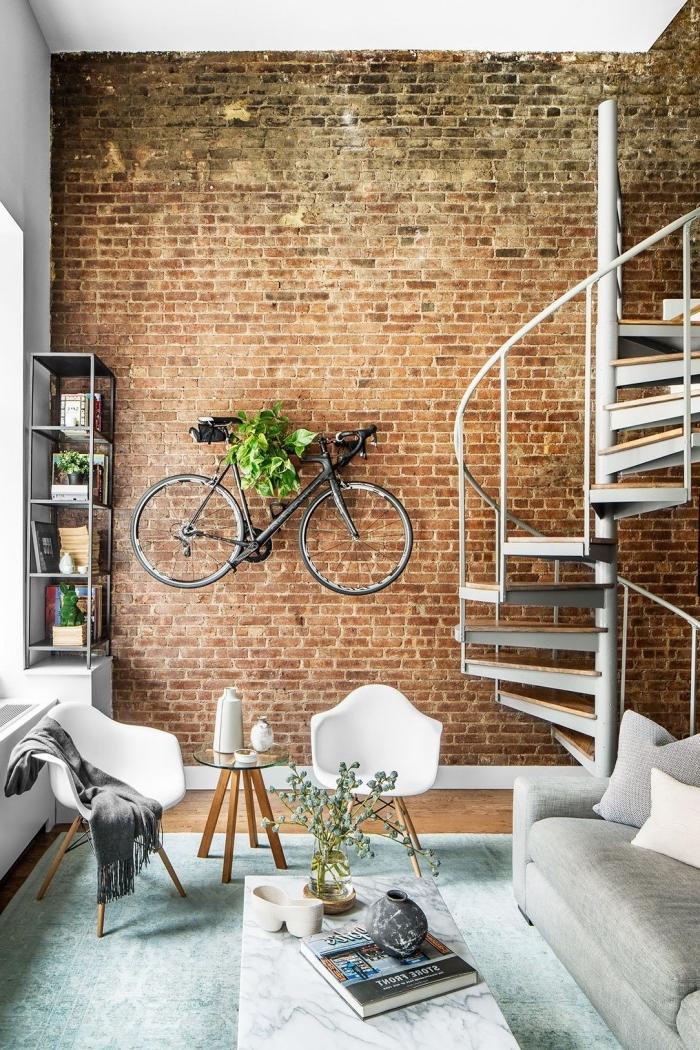 idée canapé style industriel en gris, déco de petit salon au parquet bois avec murs en briques, modèle de tapis couleur menthe