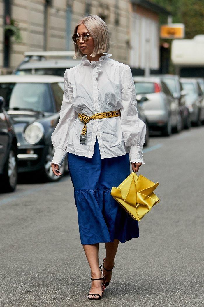 longue jupe bleue, sac jaune original, chemise blanche col structuré, ceinture originale, lunettes de soleil rondes