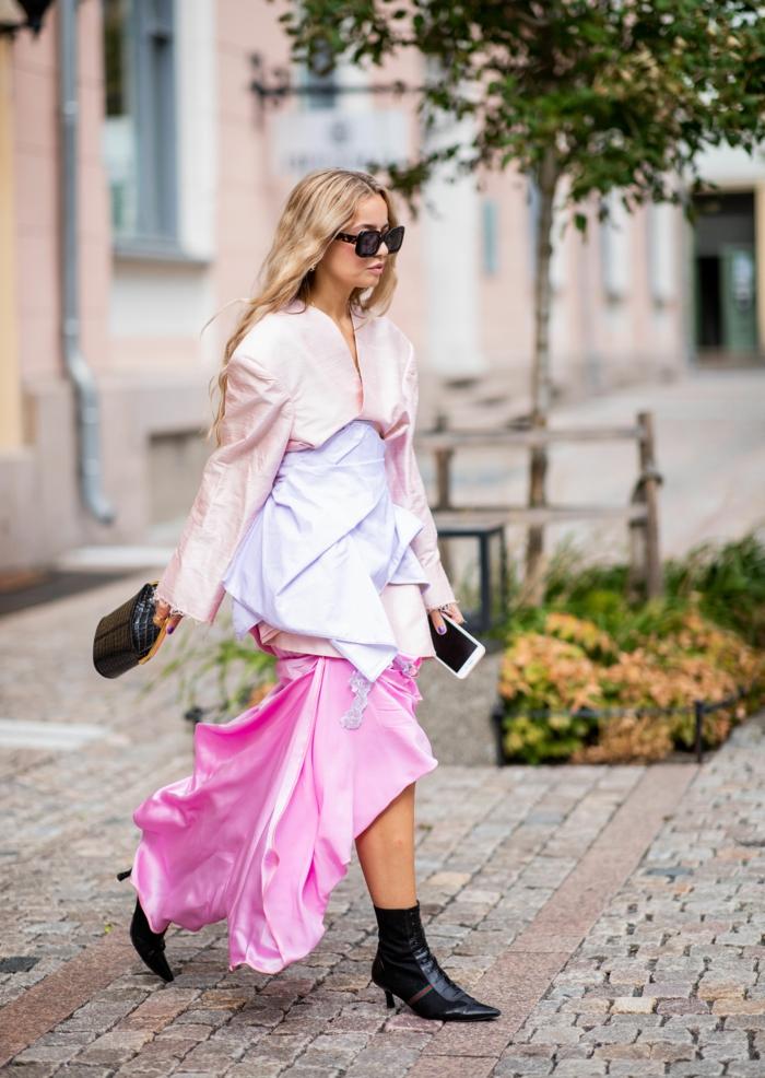 longue jupe asymétrique couleur rose, petit sac à main, bottes élégantes à haut talon, tenue de soirée femme
