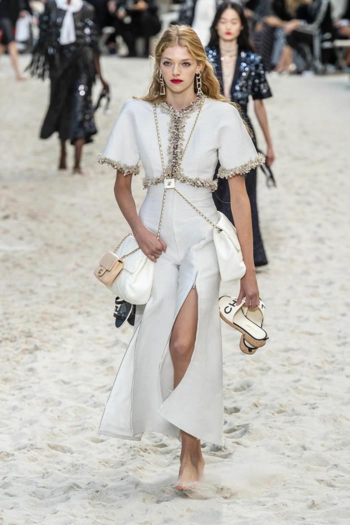 robe blanche fendue, deux sacs symétriques, sandales blanches, longues boucles d'oreille, rouge à lèvres rouge