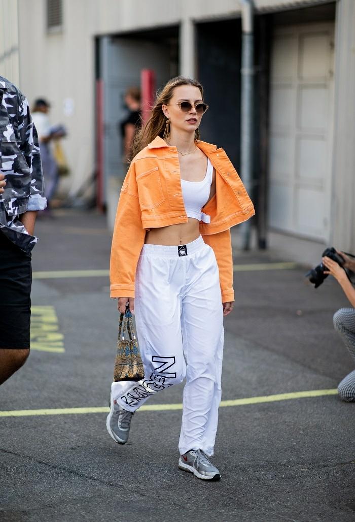 tenue de sport femme chic, veste orange, lunettes de soleil rondes, bustier blanc