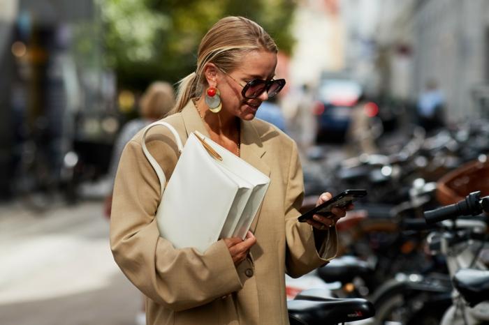 trench coat beige, grand sac à main blanc, boucles d'oreille ethniques, lunettes de soleil oversize